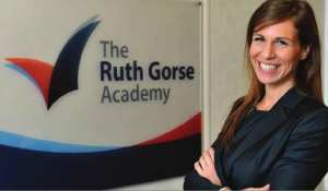 Photo of Rebekah Taylor, principal of The Ruth Gorse Academy, standing next to school's sign